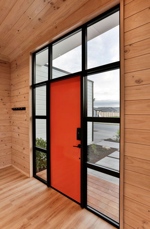 Orange front door with sidelight windows in black