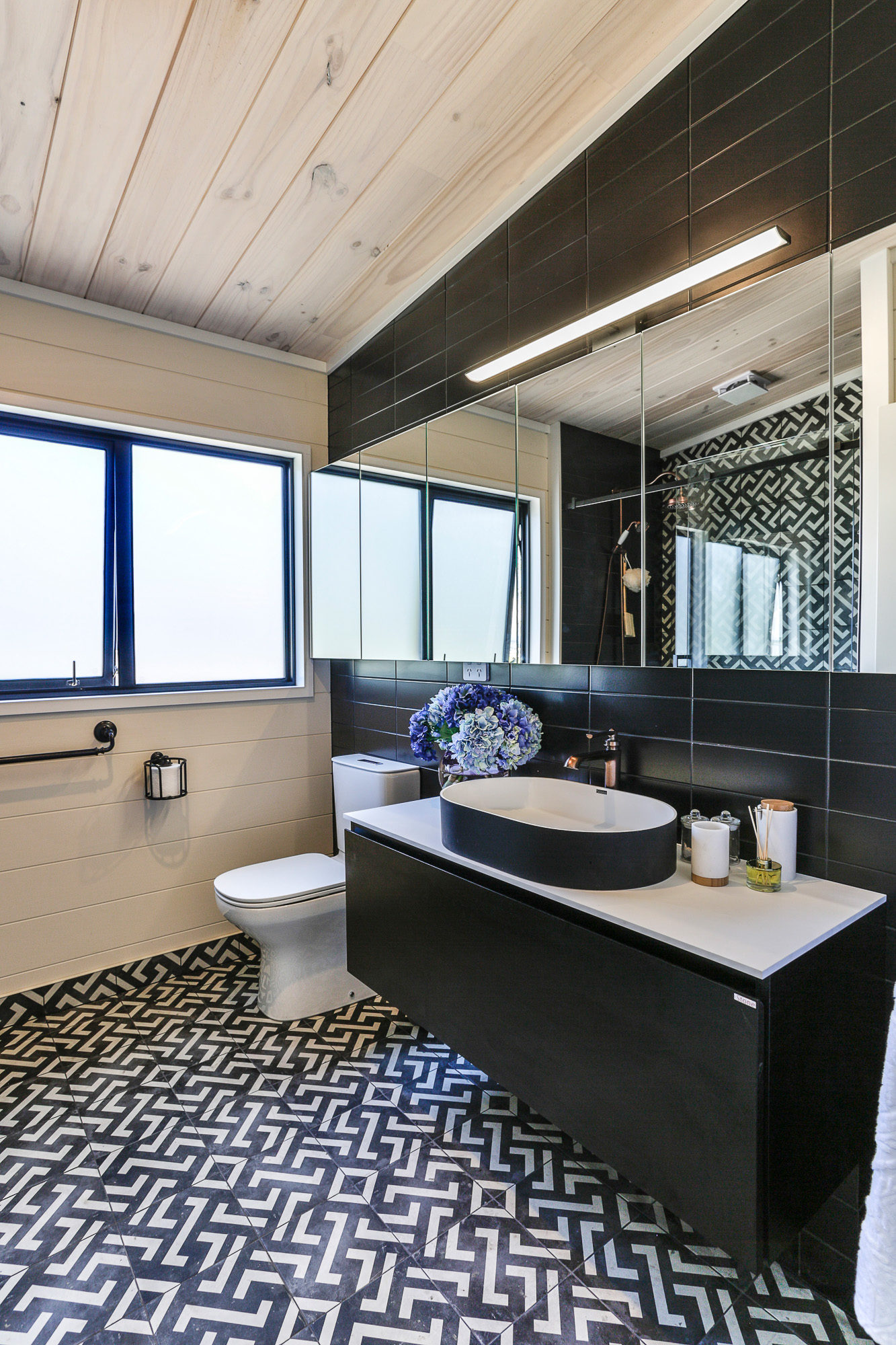Modern Lockwood home bathroom with black subway tiles and cabinetry