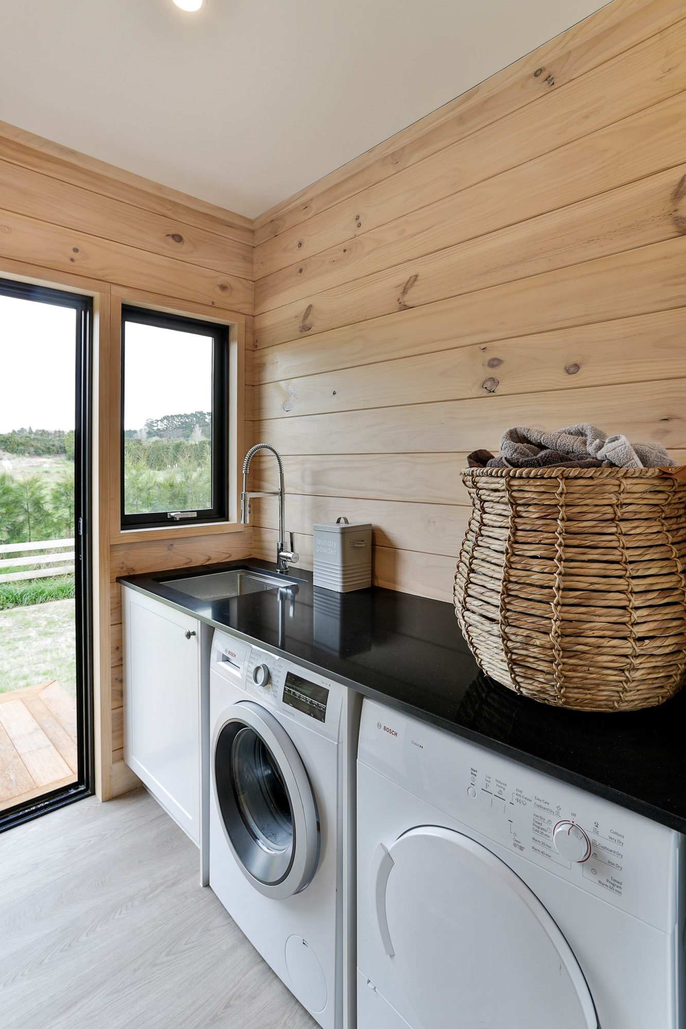 Lockwood home laundry with black stone benchtop in Papamoa
