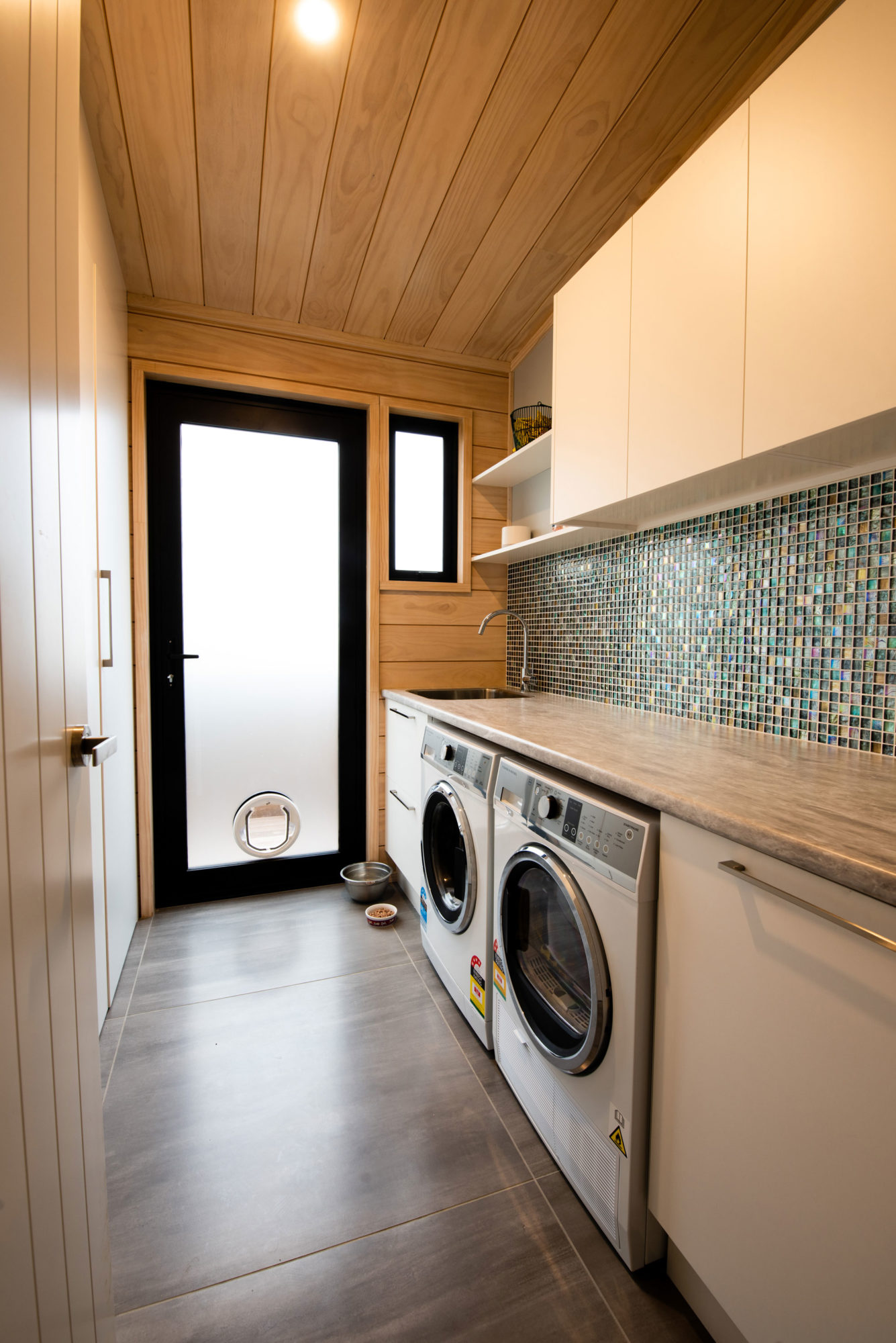 Lockwood home laundry with mosaic tiles and generous bench top