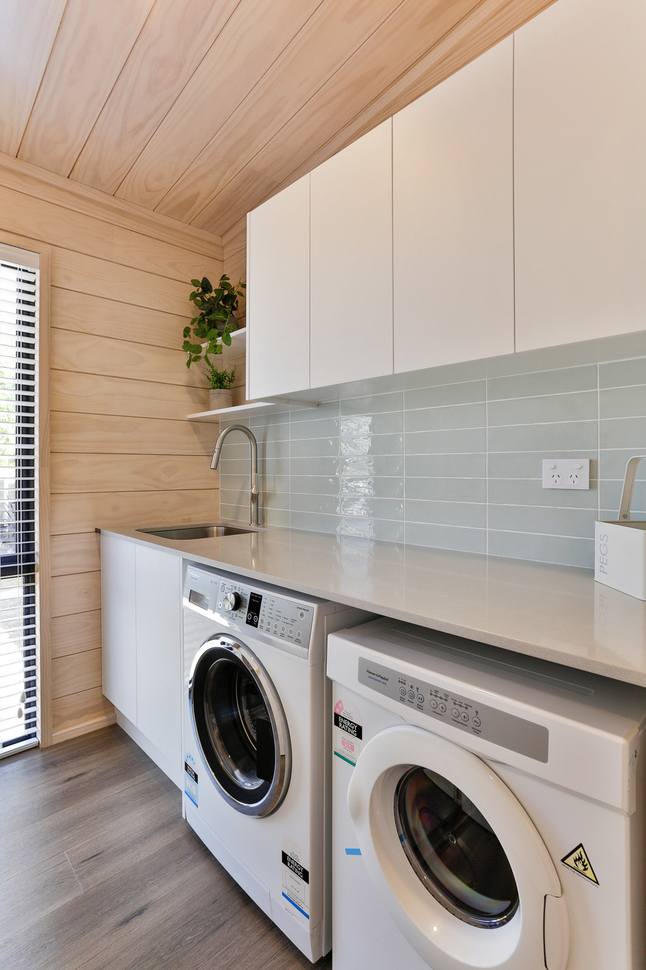 Lockwood laundry with soft blue tiles and white overhead cupboards in Wellington
